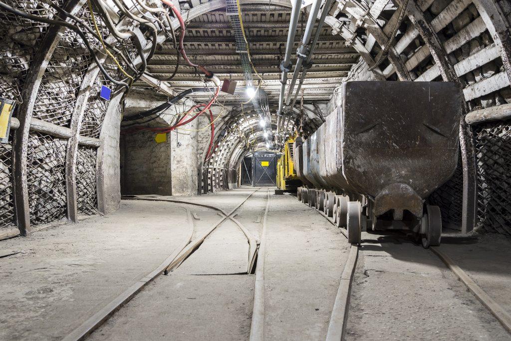 Mining carriage in underground illuminated tunnel .